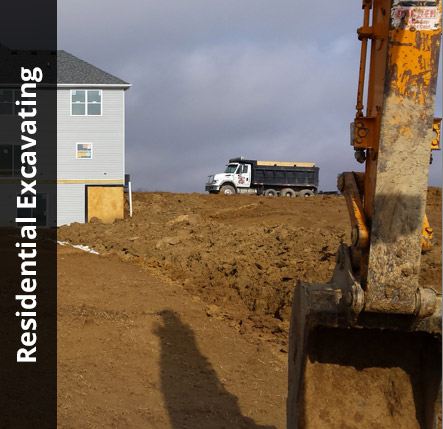 Excavator bucket in the foreground with a dump truck in the background near a house | Residential Excavating