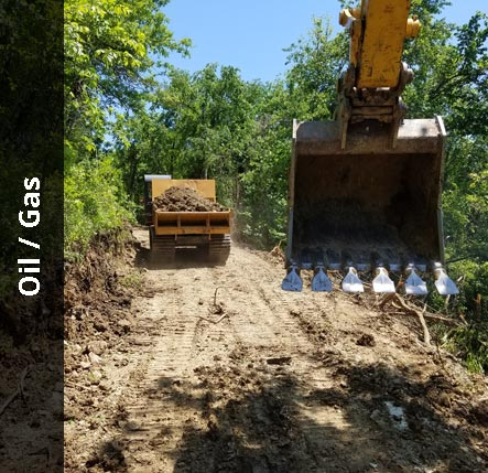 Excavator following a dump truck down an access road | Oil / Gas Excavating Services