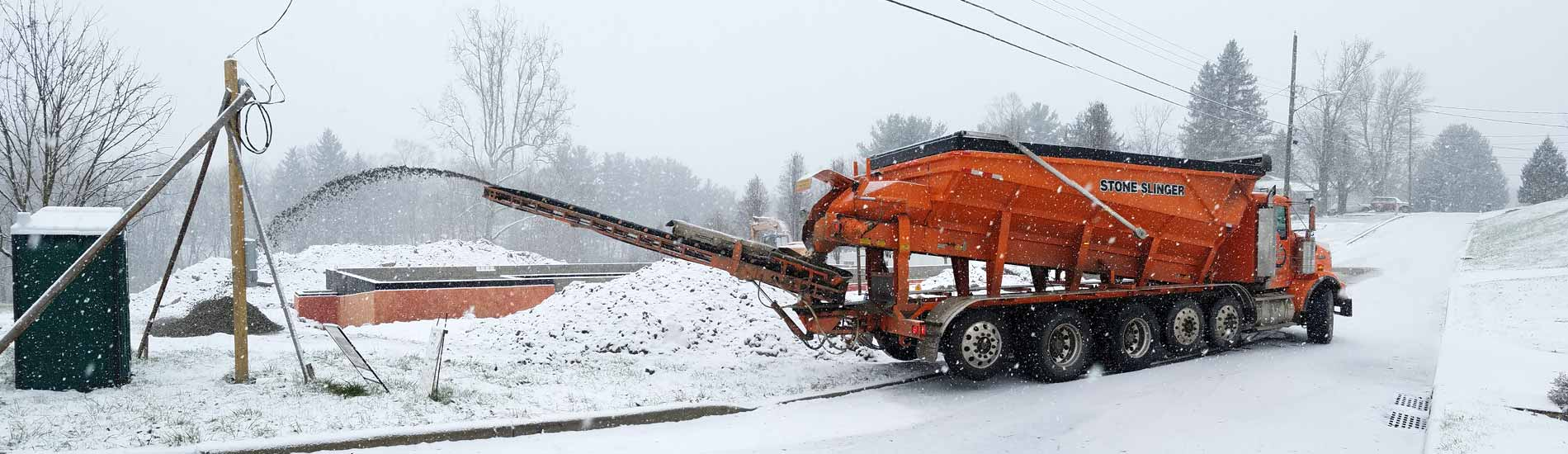 Stone slinger placing aggregate during heavy snow fall