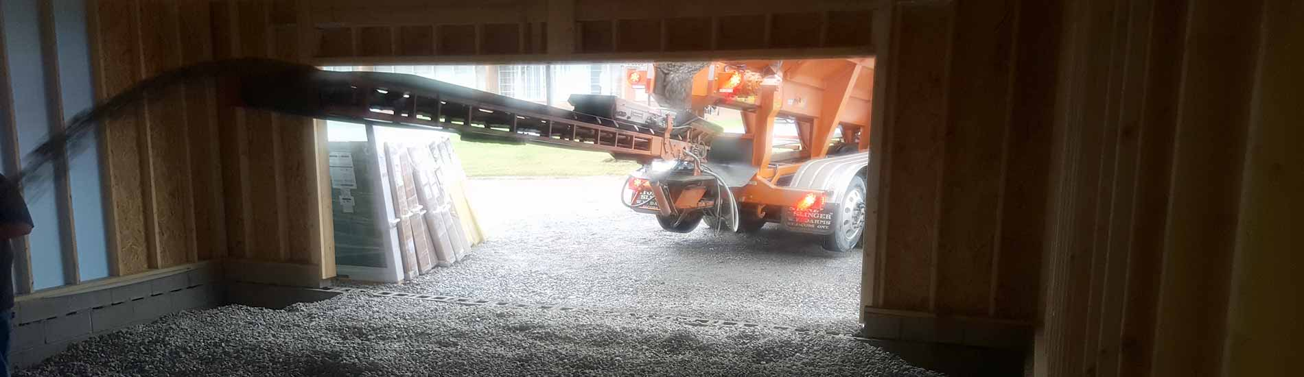 Stone slinger pouring crushed granite into a garage