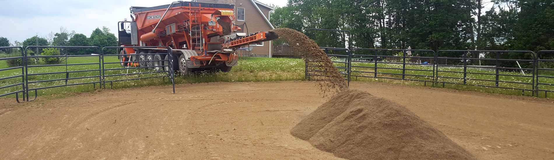 Stone slinger throwing gravel sand into a horse training ring