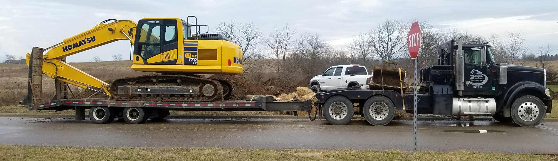 Large excavator loaded onto a flat bed trailer for hauling